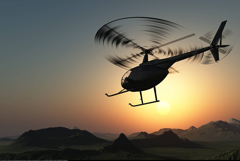 Helicopter flying in front of a sunset