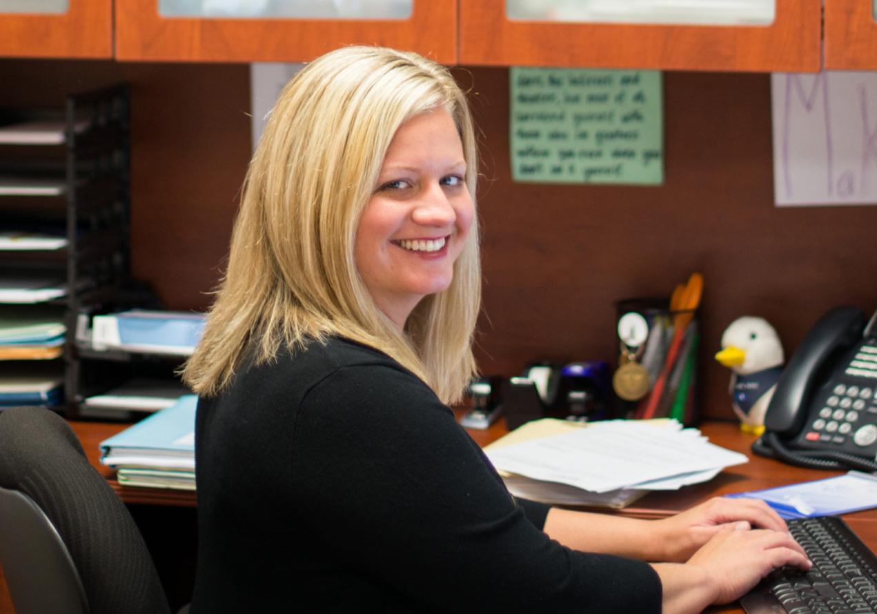 Kelly smiling at her desk