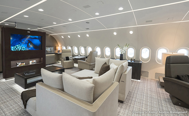 entertainment suite with tv and seating on private jet